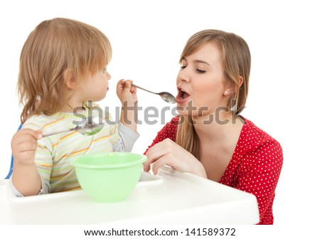 baby boy trying feed young mother, white background