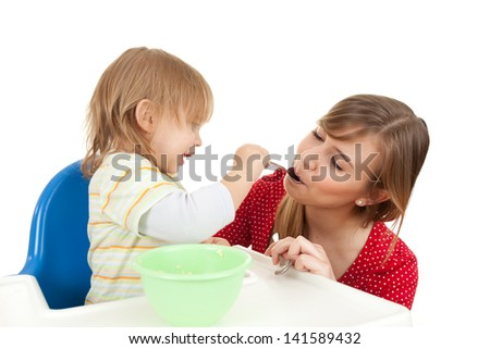 baby boy trying feed young mother, white background - stock photo