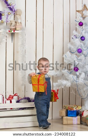 Baby boy under Christmas holiday fir tree with decorations and gifts - stock photo