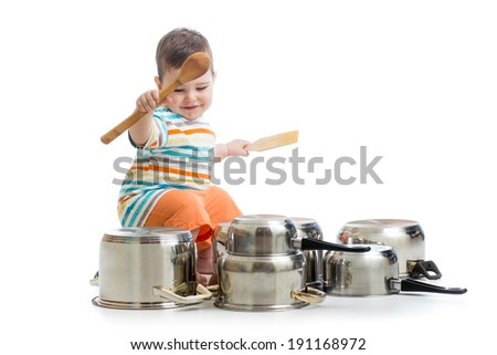 baby boy using wooden spoons to bang pans drum set - stock photo