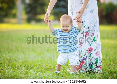 Baby boy walking in the park with mom's support - stock photo