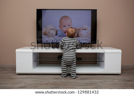 baby boy watching TV at home - stock photo