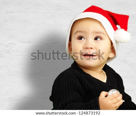 Baby boy wearing a christmas hat and looking up against a grunge background - stock photo