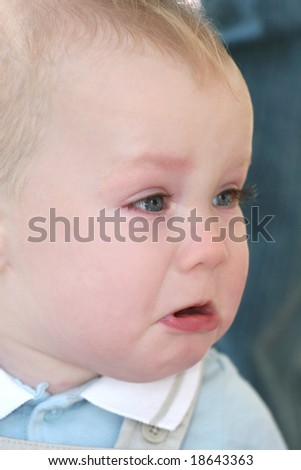 Baby boy with blue eyes and blond hair crying, portrait - stock photo