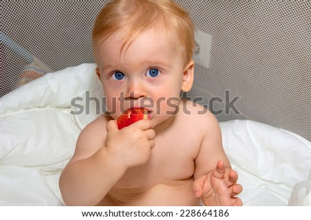 Baby boy with blue eyes eats red apple