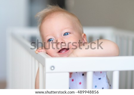 Baby boy with blue eyes standing in crib