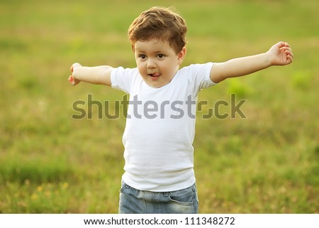 baby boy with brown hair having fun in the park, doing morning exercise. outdoor shot - stock photo