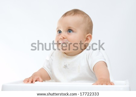 baby boy with dirty face sitting in highchair - stock photo