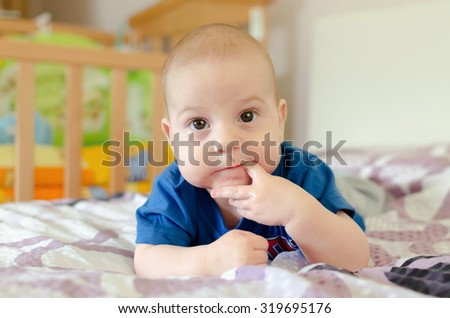 baby boy with finger in mouth