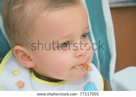 Baby boy with food hanging from his mouth