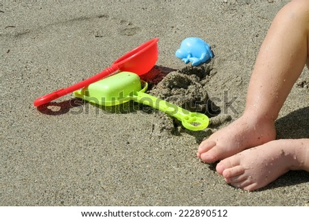 Baby boy with his toys on the beach. Boy playing on the beach. - stock photo