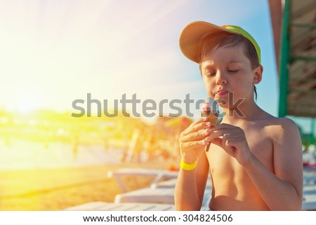 Baby boy with ice-cream at the beach - stock photo