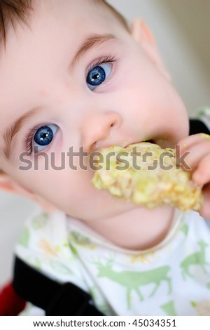 Baby boy with ricecake at mouth
