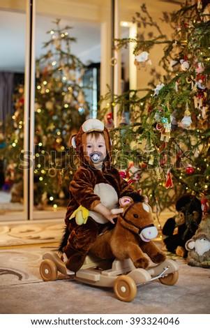 Baby boy with toy horse near Christmas tree - stock photo