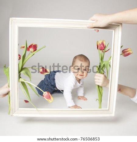 Baby boy with tulips in the  frame - stock photo