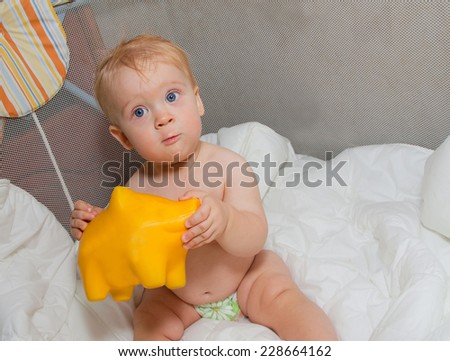 Baby boy with yellow pig moneybox in hands - stock photo