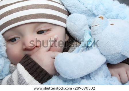 Baby boy wrapped in a soft blanket with a bear - stock photo