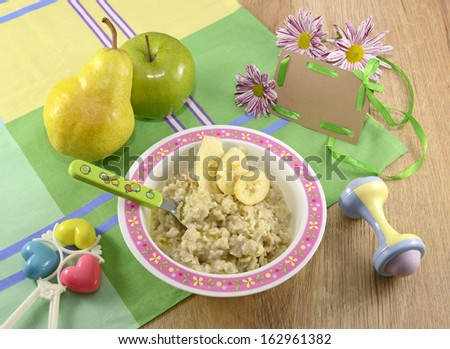 Baby breakfast with fruit and toys - stock photo