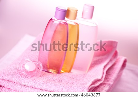 Baby care objects. Olive, shampoo, gel, towels and dummy - stock photo