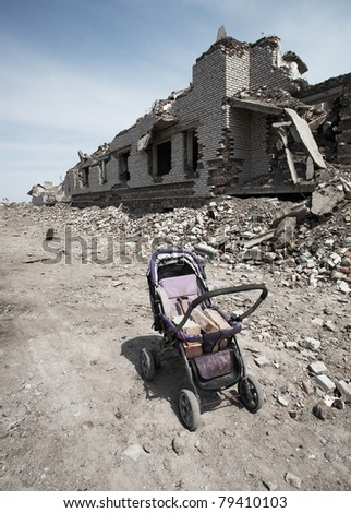 Baby carriage with bricks near the destroyed building - stock photo