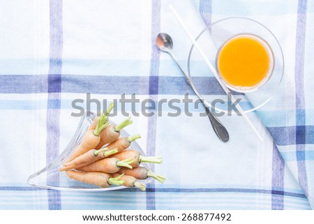Baby carrots juice glass with raw ingredient on blue table mat - stock photo