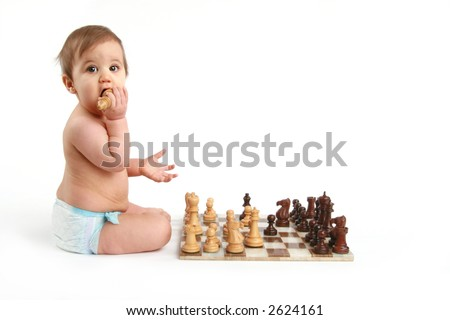 baby chewing on chess piece - stock photo
