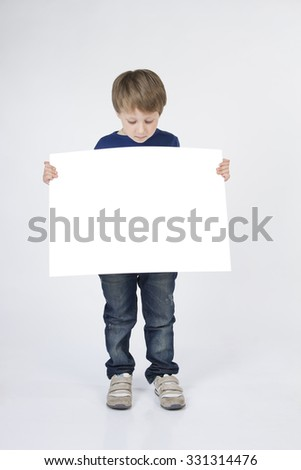 Baby, child boy holding white banner blank, board. Baby boy stands with banner in his hands. - stock photo
