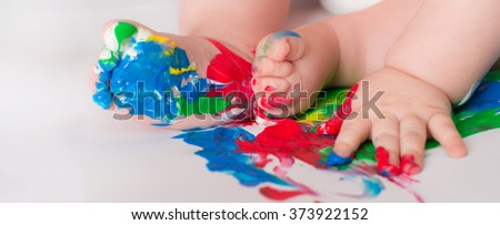 Baby child draws with colored paints hands, dirty feet.  Selective focus. - stock photo