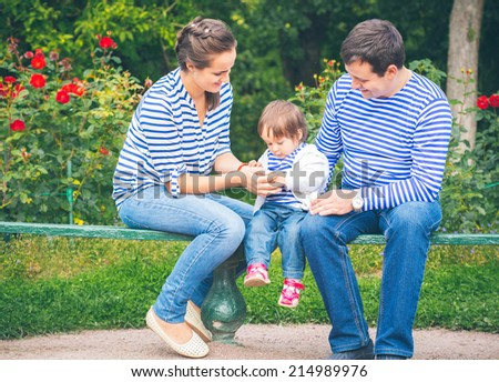baby child in park with parents on bench  - stock photo