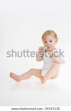 Baby clears teeth and shows consonant gesture on whites background. - stock photo