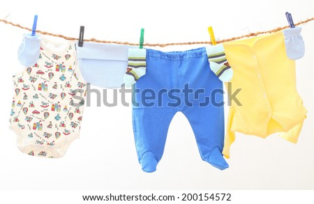 Baby clothes drying on a rope.  Kids underwear on white background - stock photo