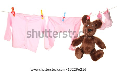 Baby clothes hanging on clothesline, isolated on white - stock photo
