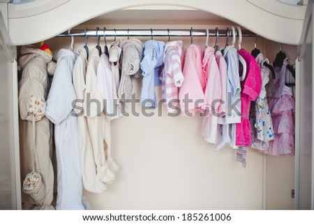 baby clothes in white cabinet - stock photo