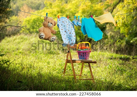 baby clothes on clothesline outdoors - stock photo