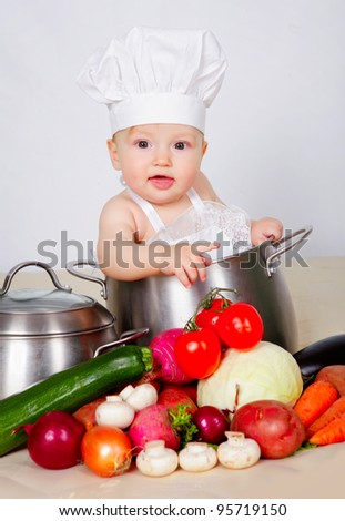 Baby cook with vegetables in studio