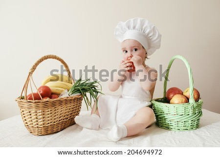 Baby cook with vegetables on kitchen - stock photo