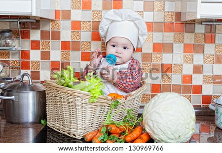 baby cook with vegetables sits in a wattled basket on a kitchen table
