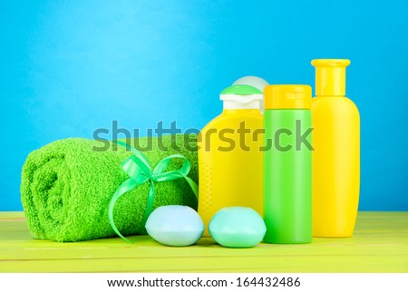 Baby cosmetics, towel and soap on wooden table, on blue background