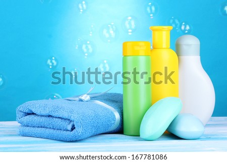 Baby cosmetics, towel and soap on wooden table, on blue background - stock photo