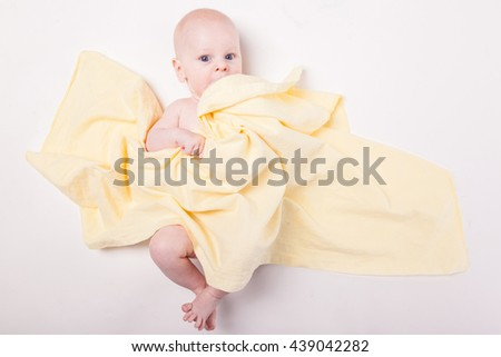baby covered with a towel on a white background from above - stock photo