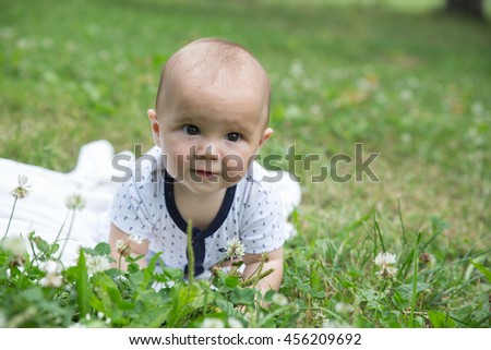 Baby crawling on the grass. Selective focus on her eyes.