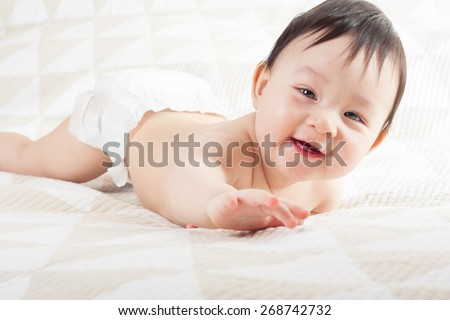 baby crawls . mladegets lying on the bed . baby smiling and lying on the bed - stock photo