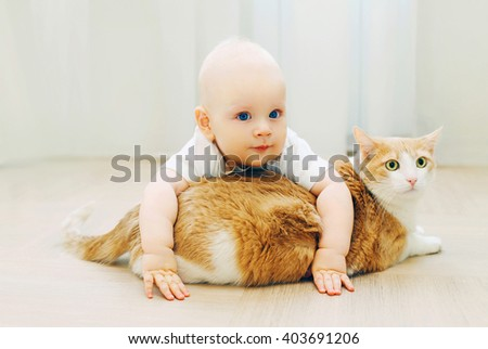 Baby crawls plays with cat at home on floor - stock photo