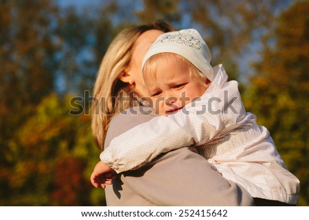 Baby crying in the arms of his mother in the park - stock photo