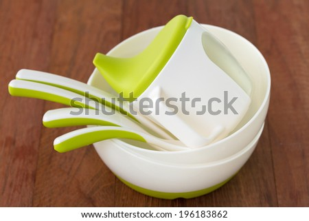 baby dishes and spoons on brown background - stock photo
