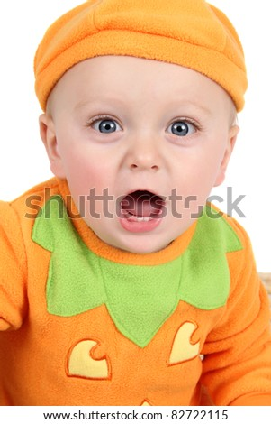 Baby dressed in a pumpkin costume on white background - stock photo