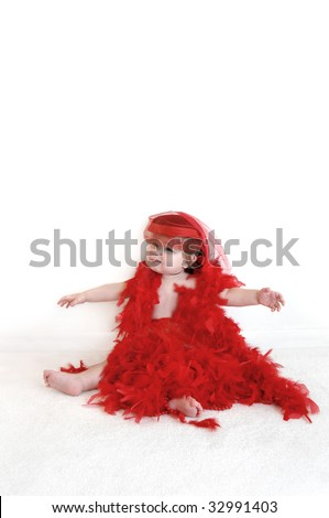 Baby dressed in red hat with netting, is not quite happy with the Boa feathers.  She is sitting in an all white room and is wearing a drape of red feathers. - stock photo
