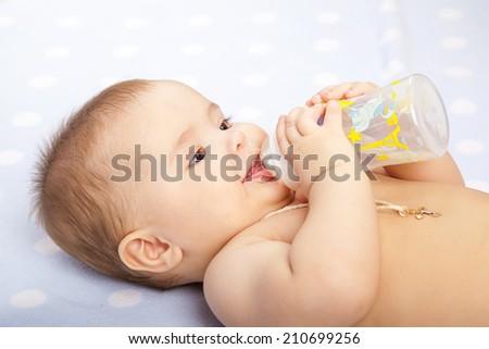 baby  drinking milk from bottle - stock photo