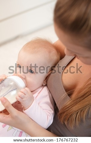 Baby drinking milk from nursing bottle, sitting on mother's lap. Photographed from above.