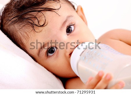 Baby drinking milk of her bottle. White background